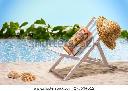 Money on vacation, pack of 50 Euro bills sitting at the beach on a sun lounger in front of a blue lagoon - stock photo