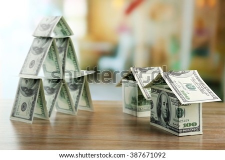 Money pyramid with money houses on wooden table, close up - stock photo