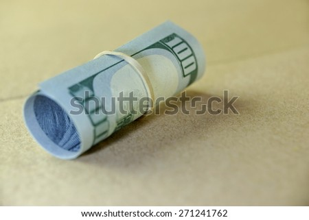 Money Roll With US New One Hundred Dollar Bill Close-up On The Beige Floor Background.  Selective Focus - stock photo
