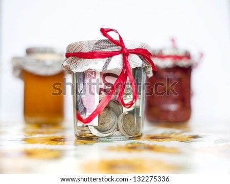 Money savings in the glass jar with preserves - stock photo