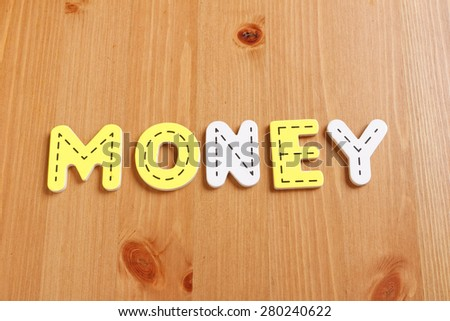 MONEY, spell by woody puzzle letters with woody background