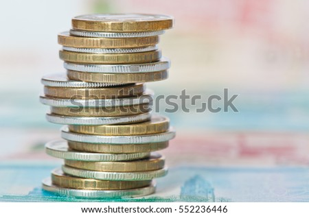 Money. Stack of rubles coins against 1000 and 5000 rubles banknotes background
