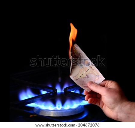 Money to burn! energy cost concept of burning a note on a gas fire - stock photo