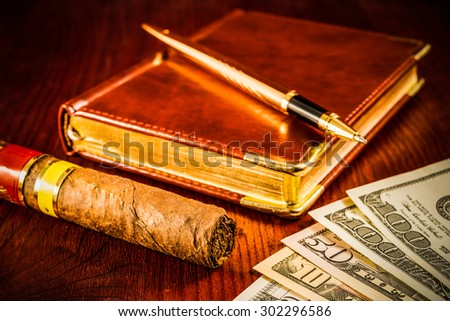 Money with a leather diary and cuban cigar with golden pen on a mahogany table. Focus on the cuban cigar, image vignetting and hard tones