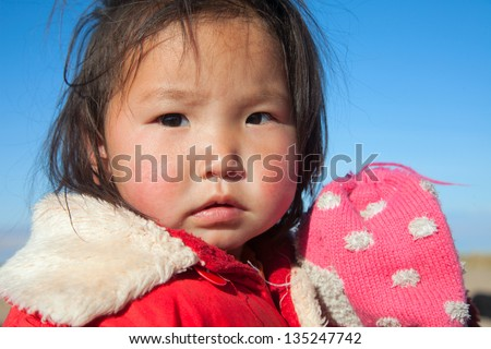 Mongolian girl is very serious-looking, the daughter of a nomad - stock photo