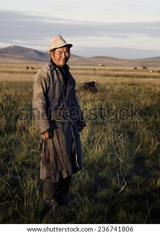 Mongolian milking man standing in a scenic view of the field. - stock photo