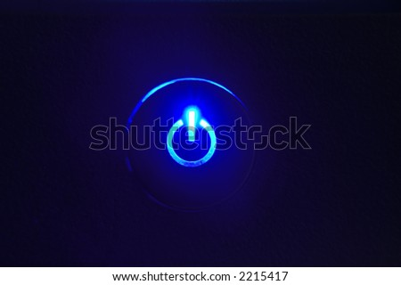 monitor power button closeup in darkness - stock photo