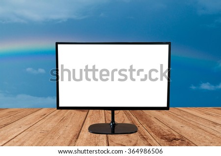 monitor with blank screen on wood planks texture and rainbow sky background for advertise - stock photo