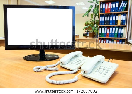 Monitor with isolated on white screen with telephones on desk in office - stock photo