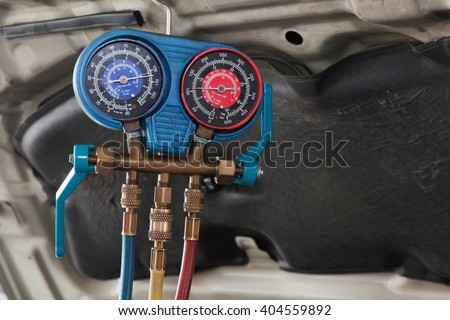 Monitoring tools for automotive air conditioning in car garage - stock photo