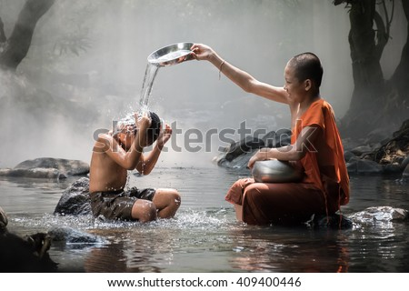 Monk and boy are have a bath water at stream. - stock photo