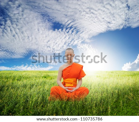 Monk meditating in grass fields and blue sky - stock photo