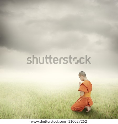 Monk pray in grass fields and rainclouds - stock photo