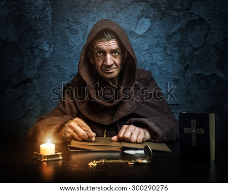 Monk - priest - front of the church holding the Bible - stock photo