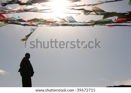 monk silhouette and tibet buddhist flag