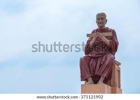 monk statue of buddhist recite scriptures - stock photo