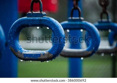 Monkey bars rings on a school playground at rainy day - stock photo