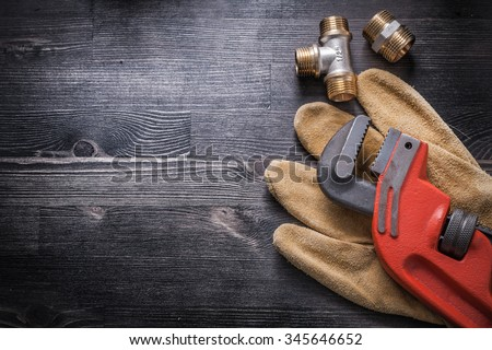 Monkey wrench brass plumbing fittings leather safety gloves construction concept. - stock photo