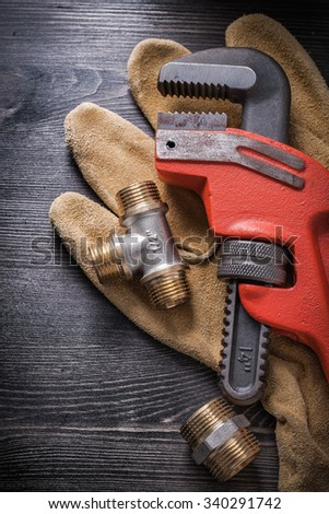 Monkey wrench plumbing fixtures protective gloves on wooden board. - stock photo