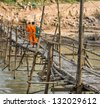 Monks on a wooden Bridge - Luang Prabang, Laos - stock photo