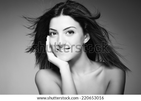 Monochromatic beauty portrait of young sexy woman against grey background - stock photo