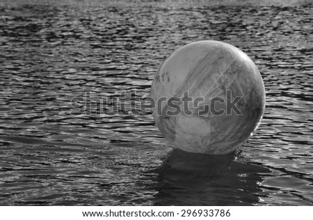 monochromatic concept image for global environmental issue using inflatable rubber ball with earth like markings and rippled water surface  - stock photo
