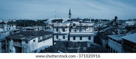 monochromatic panoramic rooftop view of the town Stonetown Zanzibar Tanzania showing buildings and tin roofs - stock photo