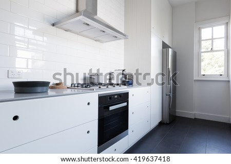 Monochrome Clean White Kitchen Bench Top And Cupboards With Appliances