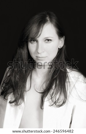 Monochrome closeup portrait of a young woman in front of black studio background - stock photo
