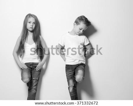 monochrome fashion portrait of beautiful little couple. beauty girl and boy - stock photo