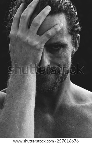 Monochrome greyscale portrait of a handsome bearded man holding his head in remorse or regret with a rueful smile - stock photo