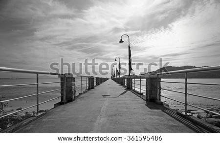 Monochrome image of a dramatic cloudy sky over a long boat jetty to Jerejak Island in Penang, Malaysia. - stock photo