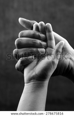 Monochrome image of a hand of a mother holding a child's hand. Ideal for concepts of care and love. - stock photo