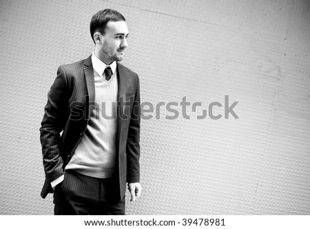 Monochrome image of a young business man posing on wall - stock photo