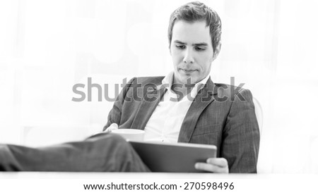 Monochrome image of pensive young business executive with his feet on the desk enjoying a cup of coffee as he is looking at  his tablet computer. - stock photo