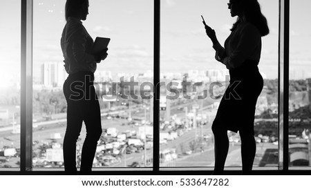 Monochrome image. Silhouettes of two young businesswomen standing against window. First woman holding smartphone, second digital tablet. Window is visible urban landscape. Girls using gadgets.