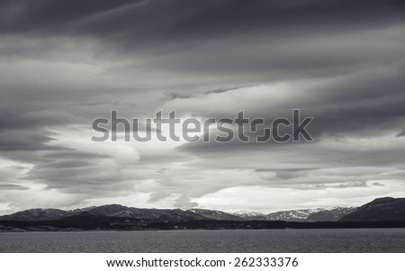 Monochrome Norwegian coastal landscape with sea and dramatic stormy sky - stock photo