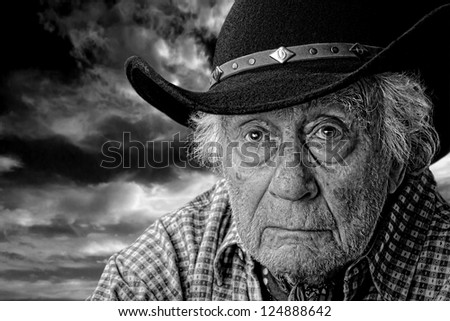 monochrome of an old man wearing a black felt hat against a stormy cloudy sky - stock photo