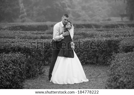 Monochrome photo of groom hugging bride at cold day - stock photo