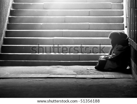 Monochrome photo of homeless woman reading the book in subway under the sunlight - stock photo