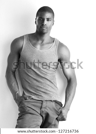 Monochrome portrait of a cool young male fashion model posing against white background - stock photo