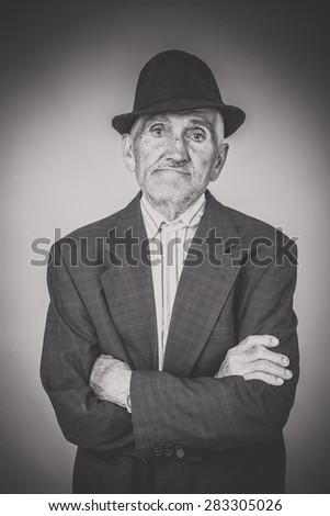 Monochrome portrait of expressive old man with arms folded  - stock photo