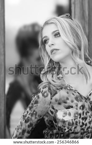 Monochrome portrait of urban woman posing in front of shop window - stock photo