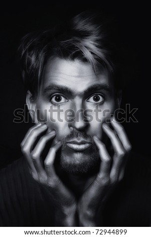 monochrome portrait of young attractive man with a silvery makeup on her face and hands against a black background