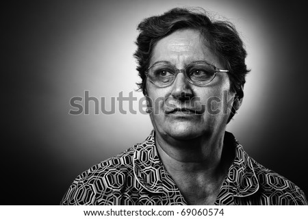 Monochrome toned closeup portrait of a senior woman with glasses - stock photo