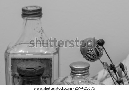 Monochrome view of Victorian era hairpins, with equally old boudoir bottles.