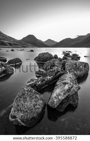 Monochrome view of Wastwater in the Lake District at sunrise with rocks and boulders in foreground. - stock photo