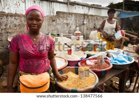MONROVIA, LIBERIA - FEBRUARY 19: A woman stands in front of her roadside stall where she sells grains in Monrovia, Liberia on February 19, 2012.  - stock photo