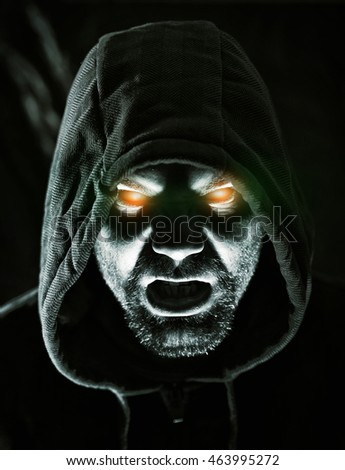 Monster in hood with glowing eyes