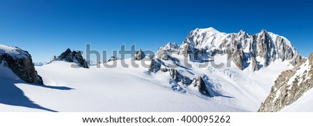 Mont Blanc, France: winter panorama on the east face from Geant Glacier. On the right the pinnacles of Mont Maudit. On the left the upper station of the Skyway cable-car from Courmayer, Italy. - stock photo